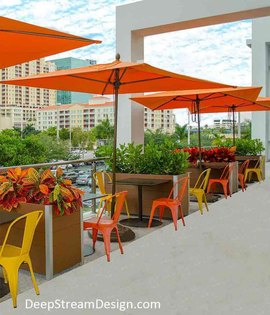 Movable Commercial Wood Planters crafted from maintenance free, redwood colored recycled plastic lumber separate tables under orange umbrellas along a restaurant's outdoor balcony seating area.