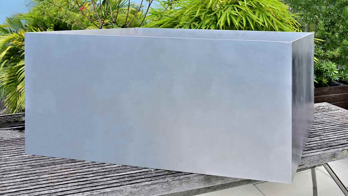 """Custom modern large, 48"""" long X 36"""" wide X 24"""" high, rectangular aluminum planters crafted from 5086 marine alloy aluminum with a flawless natural finish shown on a tropical roof terrace."""