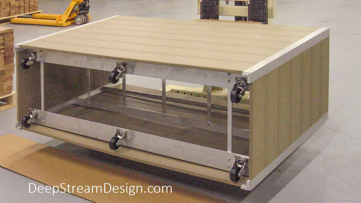 Photo of a large, tall wood garden planter with wheels laying on its side in DeepStream's shop showing how the hidden caster wheels are bolted on to the structural aluminum frame that also supports the separate planter box and the waterproof planter liner.