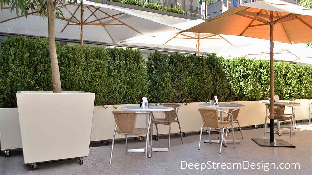 Extra-large, modern, rectangular, and tapered outdoor planters with wheels create a hedge wall and dividers between tables at the summer outdoor restaurant found at NYC's Rockefeller Center Plaza.