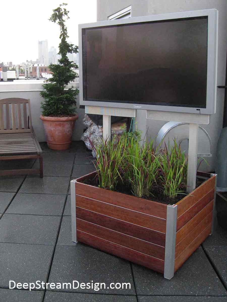 An urban penthouse roof terrace has a large outdoor TV mounted above a landscaped large wood planter on wheels in keeping with the natural calming environment that this owner is creating.