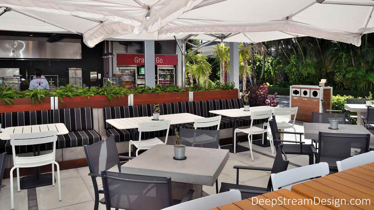 Tall movable rectangular wood Planters on Wheels create a divider between food service and dining areas under large white umbrellas at an upscale outdoor restaurant on a tropical island.