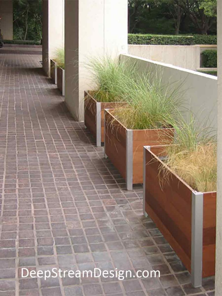 A row of modern rectangular Commercial Wood Planters, landscaped with tall ornamental grasses, line a portico of a residential building leading to a parking garage.