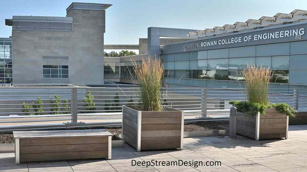 """Modern Custom 36"""" square Commercial Wooden Planters with a companion Museum Bench on an upper outdoor deck of a College of Engineering building, complementing the building's modern geometric architecture."""