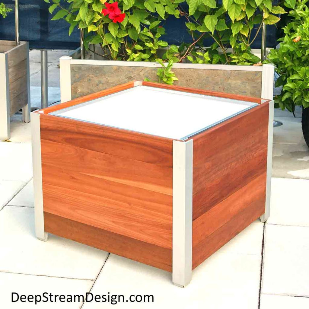 A square Commercial Wood Planter with waterproof liner in front of a rectangular garden planter with trellis on a tropical roof deck.