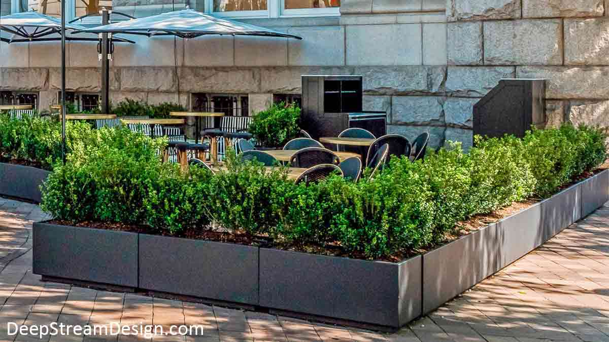 Rectangular dark bronze painted aluminum planters landscaped with bushes are arranged to create a sidewalk cafe under large umbrellas on a city plaza next to an historic building made with massive blocks of granite.
