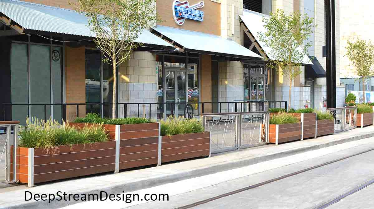 A series of long modern square and rectangular Wood Garden Planters of varying heights, planted with tress and ornamental grass, line an urban sidewalk acting as a safety barrier between the sidewalk and autos on the street.