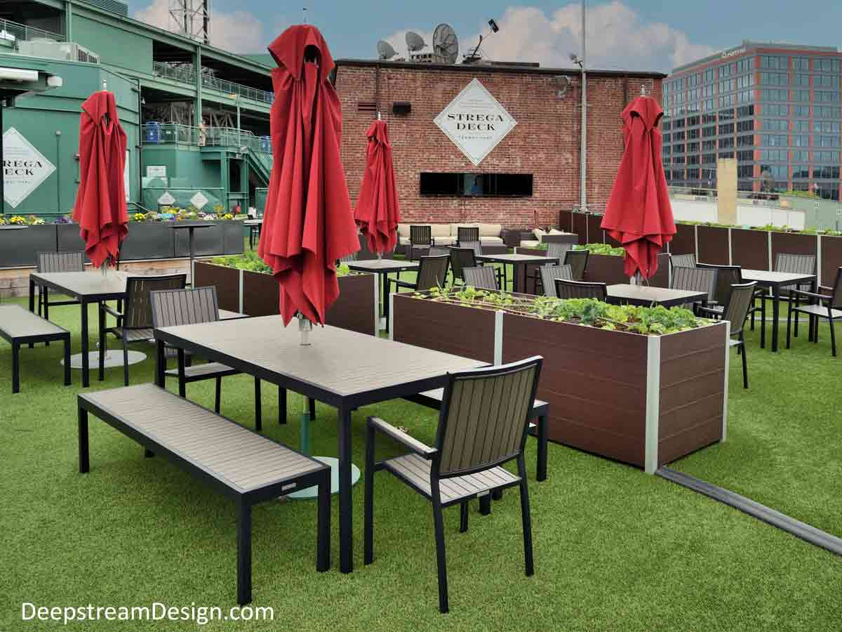 Ipe brown recycled plastic lumber Commercial Wood Planters with food safe waterproof liners growing produce separate seating areas of a farm-to-table restaurants outdoor roof terrace dining area under red umbrellas.