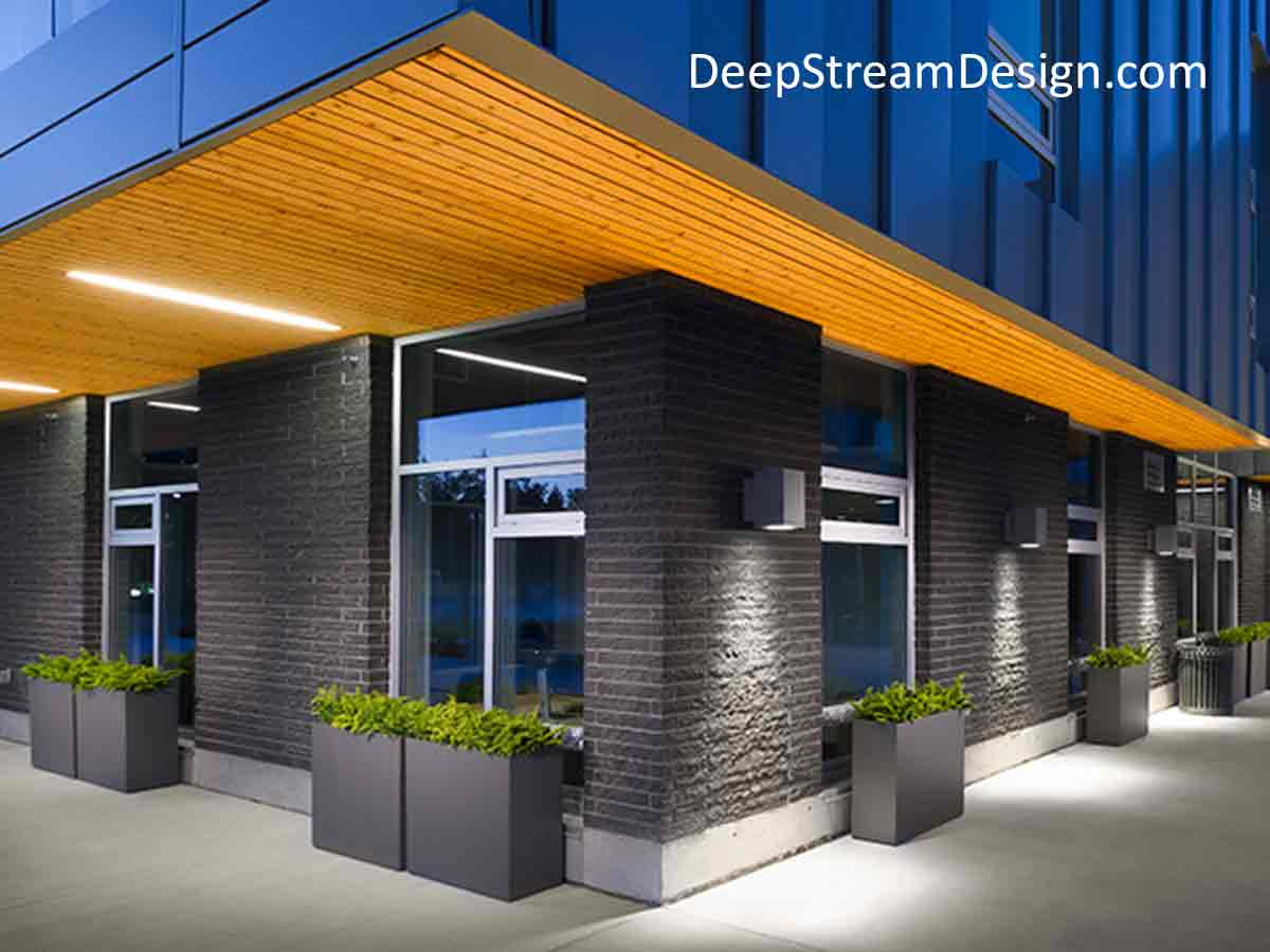Several tall rectangular Aluminum Planters rest on a sidewalk against a building under lights at dusk accentuating the crisp modern architectural lines of a commercial building.