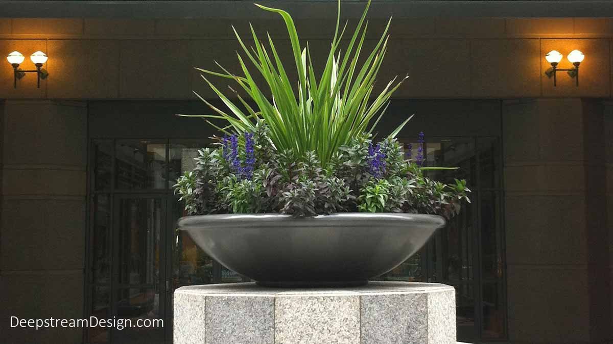 A single large beautifully landscaped saucer shaped commercial Arcade Fiberglass Garden Planter creates a dramatic entrance on a granite pedestal centered in front of the double wood and glass paned entrance doors to a classic stone building.