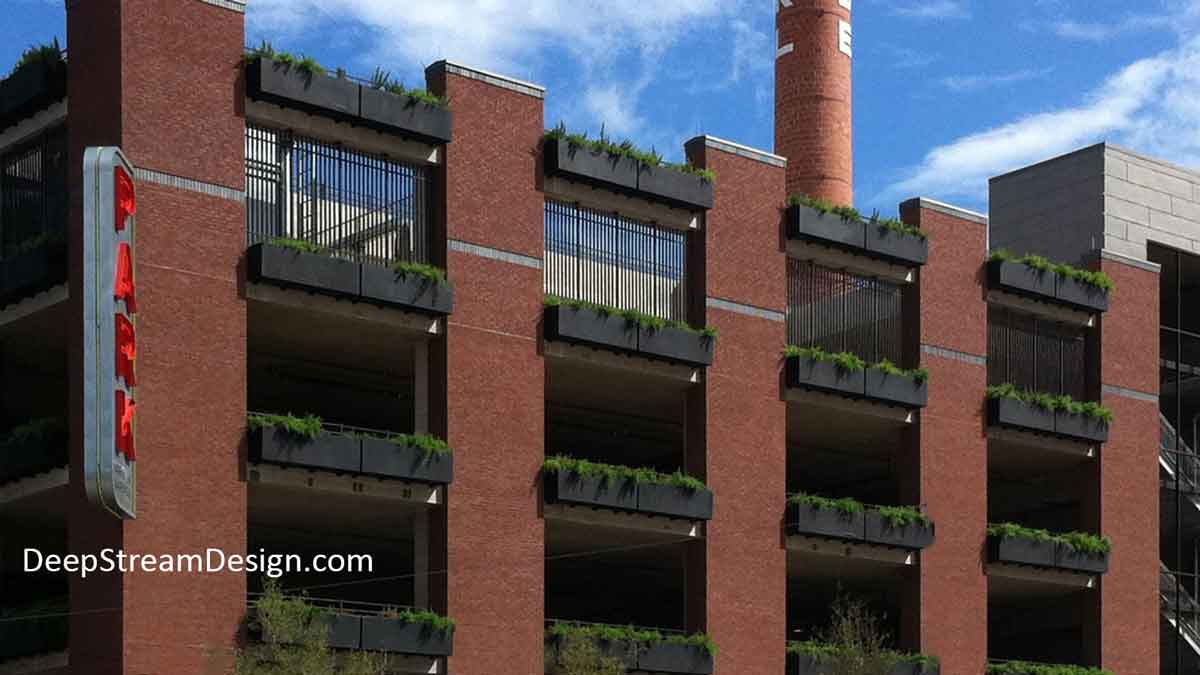 Architectural Bronze colored lightweight fiberglass Commercial Hanging Garden Planter Boxes overflowing with green plants, are mounted with pre-engineered brackets to the railings on every level of a red brick parking garage wall of a historic brewery, adding a natural visual interest.