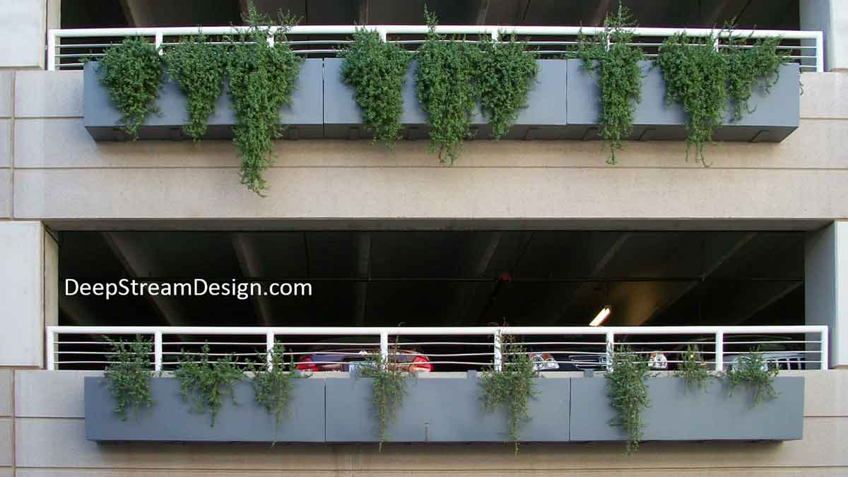 Soft grey lightweight fiberglass Commercial Hanging Garden Planter Boxes, overflowing with green, are mounted with pre-engineered brackets over the poured in place structural parapet walls that protect openings in an otherwise blank parking garage wall.