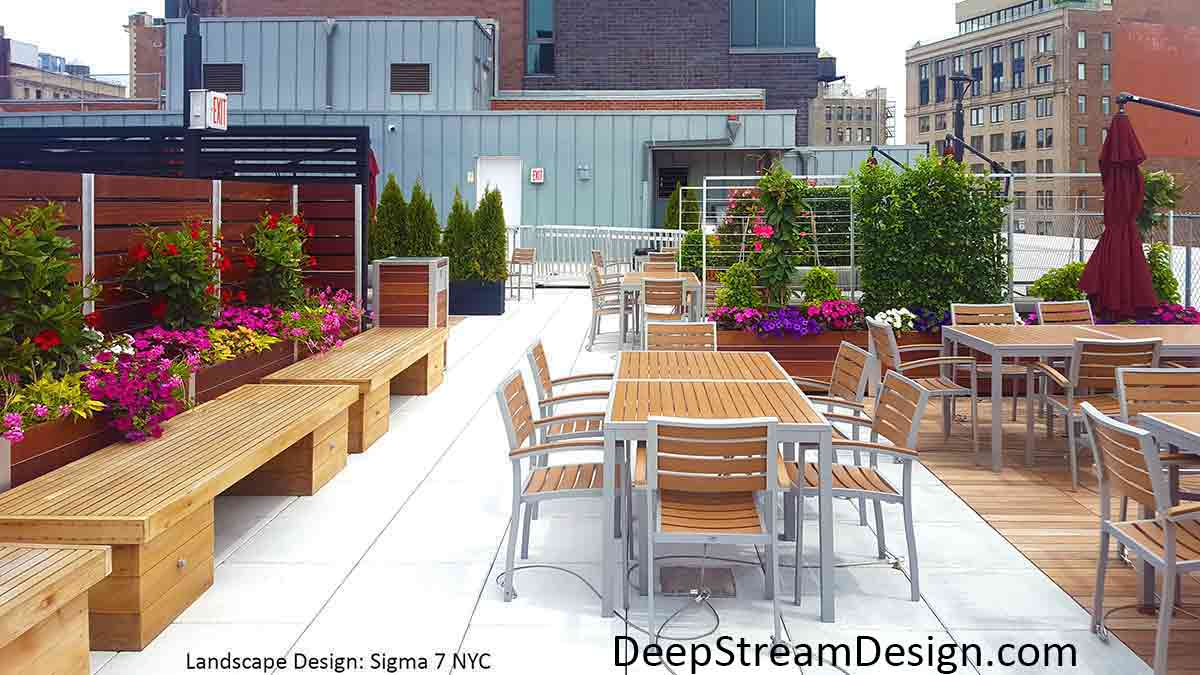 Large Wood Garden Planters with screen wall and trellises full of bright colorful flowering plants are a beautiful way to create privacy and separate seating areas on an urban restaurants roof deck dining area.