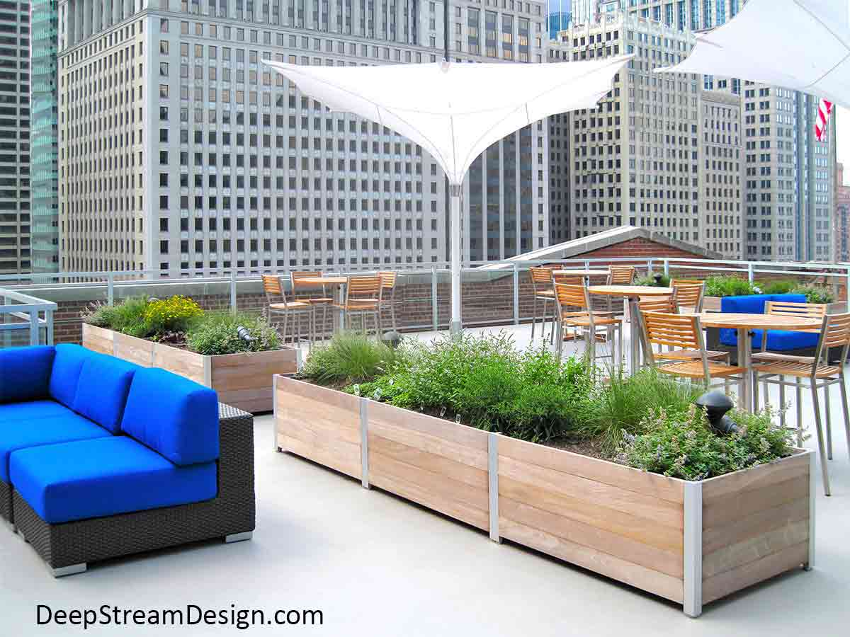 Commercial planters create a living wall full of herbs with the planters acting as outdoor planter divider for a hip modern conversion of a historic warehouse into urban rooftop restaurant surrounded by high-rise building. The long planters separate the modern tables with wood and aluminum chairs from a lounging area with blue couches overlooking the Chicago River in the Loop.