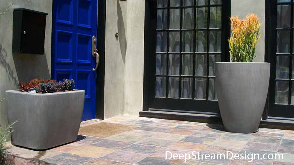 The Downtown collection of large high quality Concrete Planters have distinctive curves and soft corners that combine with their elegant proportions to create a contemporary flair. Here a tall round and shorter rectangular concrete planter flank a bright blue raised panel door and traditional floor to ceiling glass windows outside this traditional, Southwest residence.