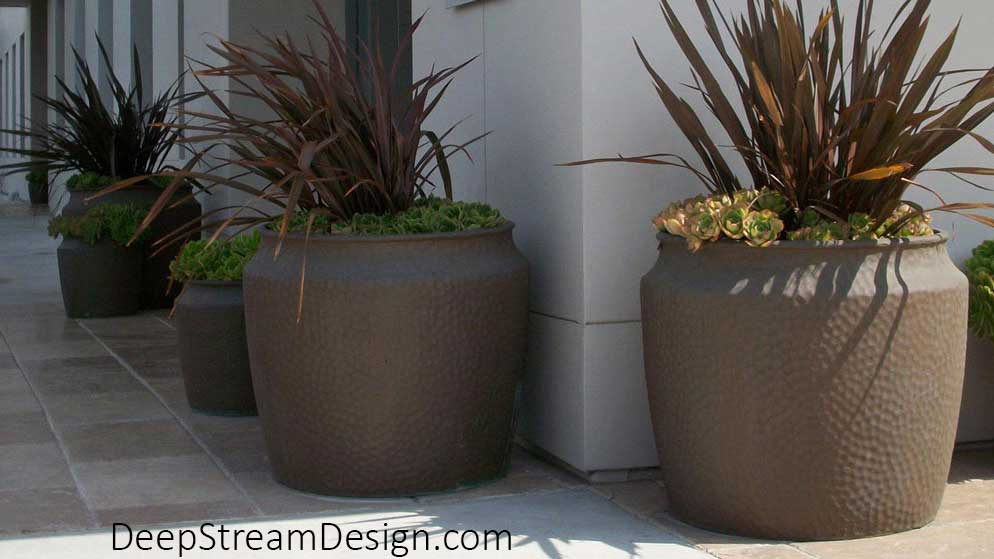 """A series of round and square arts and crafts inspired """"hammered"""" copper texture Fiberglass Garden Planters with a metal-infused finish line a steep village path providing old world charm."""
