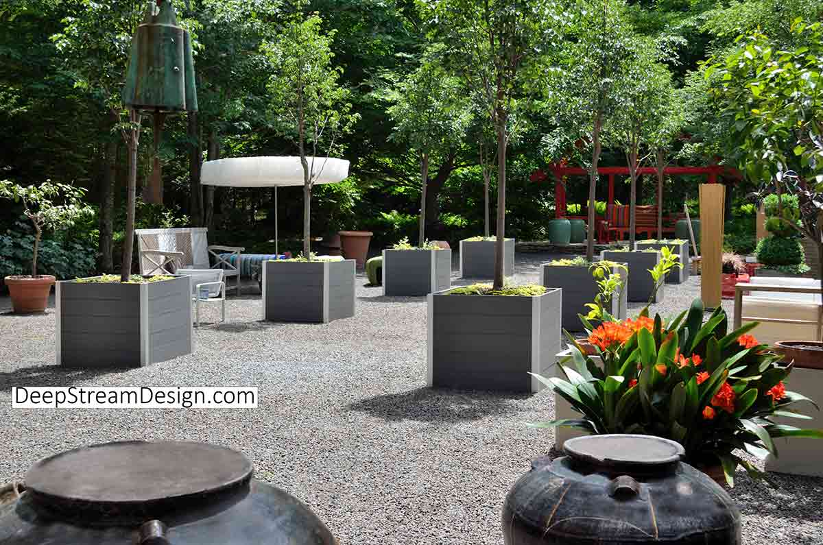"""Eight 36"""" square cube Large Wood Garden Planters with strong rotomolded planter liners hold trees in a forest clearing of a botanical park with flowers."""