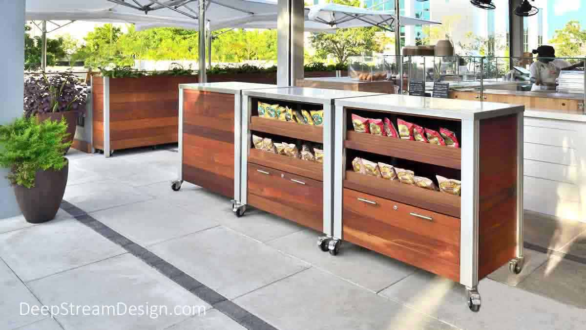 Custom outdoor restaurant food service carts and tall, wood planters on wheels create a casual up-scale tropical island outdoor restaurant under bright white umbrellas and blue skies with a flexible floor plan and open kitchen .
