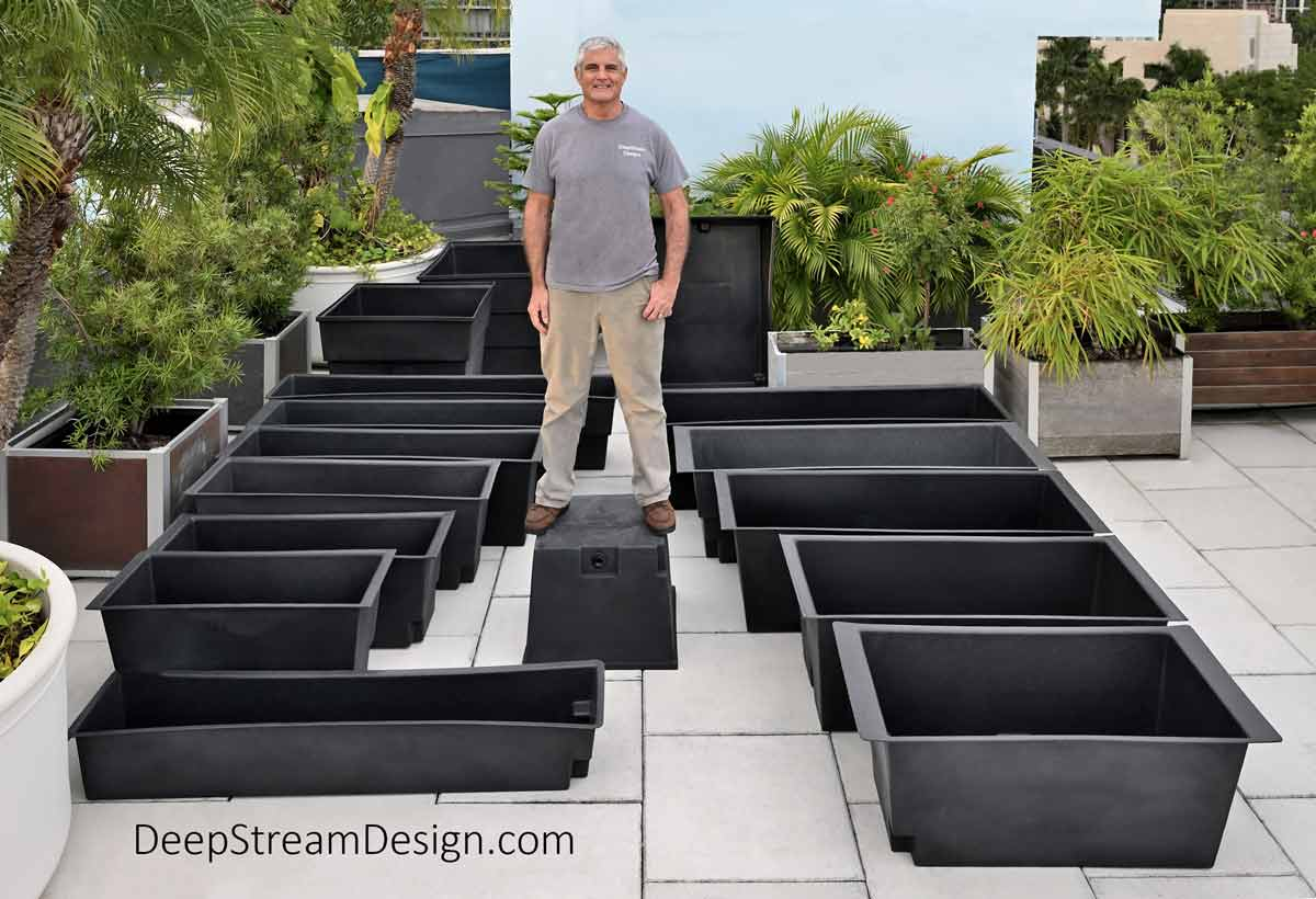 16 different size and shaped commercial planter liners are displayed on a tropical roof top deck landscaped with green palms trees, bamboo, and podocarpus. A large man is standing on top of one of the garden planter liners to show how strong they are.