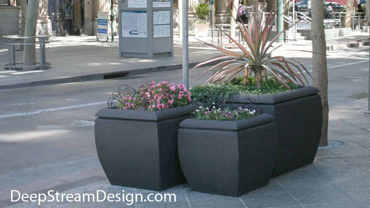A series of 3 Downtown cube shaped grey high quality Concrete Planter of varying heights and volumes makes bright and protective cluster for pedestrians on the sidewalk of a busy street.