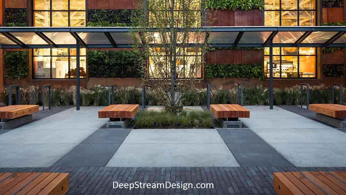 The wall behind a sleek modern Zen like rectilinear exterior seating area of the equally modern yet rustic Slabtown Marketplace in Portland, Oregon, is complemented with dark green foliage grown without soil inside rectangular blocks of Tournesol VGM® modular Live Wall System mounted to the exterior.