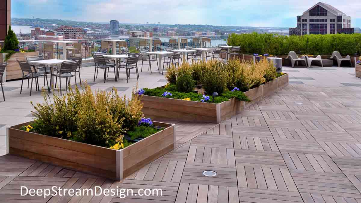 Several lushly landscaped extra large planters atop the 13th floor award winning world class roof terrace of the historic Exchange Place building overlooking the famous Boston Clock Tower and Boston's Inner Harbor on a clear sunny spring day.