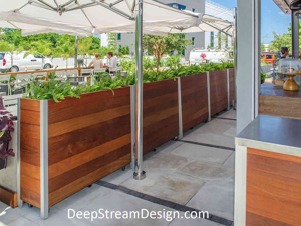 Tall, movable, very Large Wood Garden Planters create a casual outdoor restaurant, under sunny bright blue tropical skies with overlapping white umbrellas.