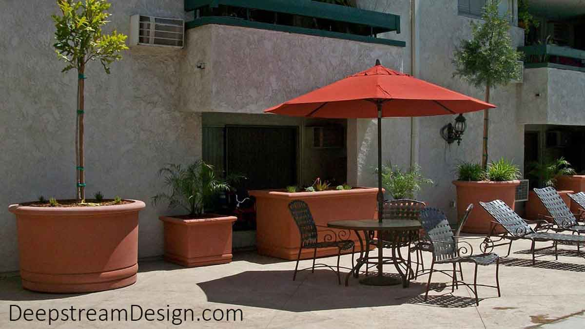 The Florence Collection is Renaissance revival in terracotta colored high quality concrete planters and pots with rounded scroll-top. The round accents in the lower portion are an elegant addition to the design, imparting a Mediterranean influence on these 6 very large round and rectangular concrete garden planters, seen here on a pool deck.