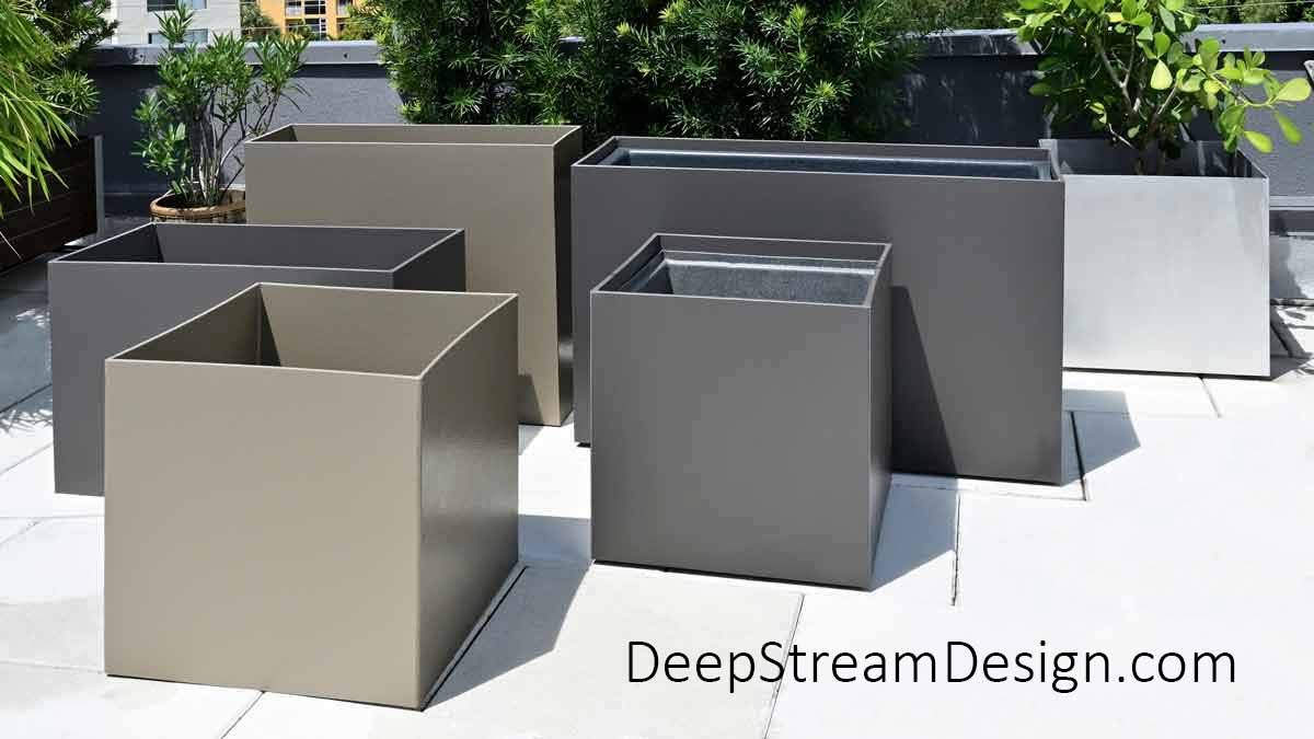 6 empty square and rectangular modern bronze and slate colored Food Safe Plastic Planters with planter liners arranged on a roof deck in front of tropical landscaping.