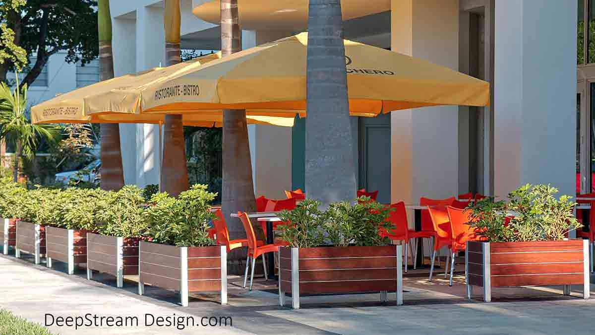 Several Wood Garden planters landscaped with green bushes surround modern silver metal tables and bright red modern chairs under bright yellow umbrellas create one of Miami cool tropical sidewalk cafés in a upscale neighborhood..