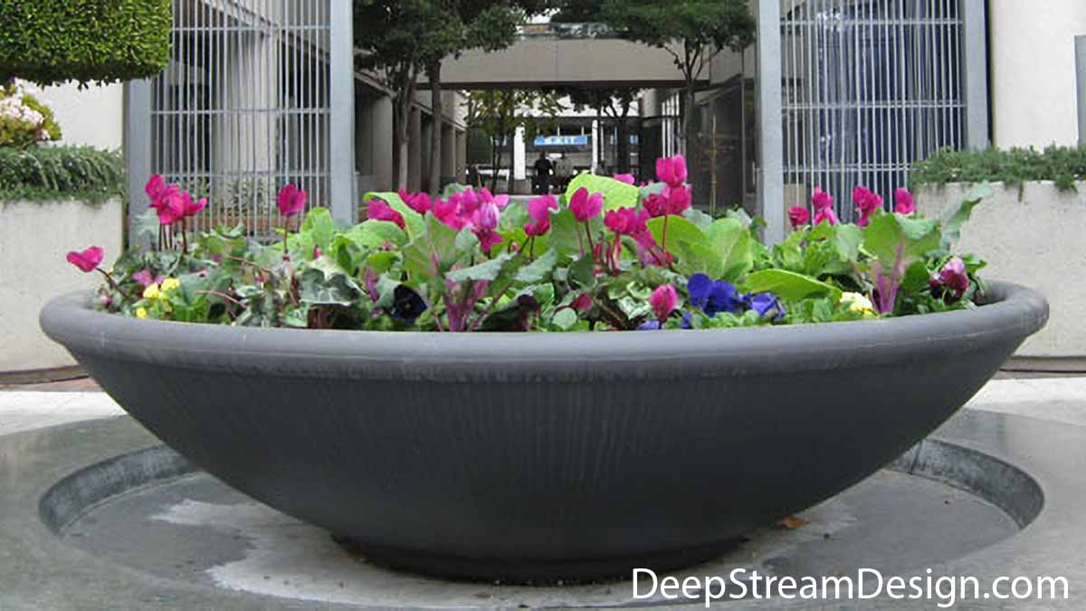 A single, very large, brightly landscaped saucer shaped high quality commercial Downtown Concrete Planter, positioned in a complementary depression centered in front of the double steel rod gate entrance to a transit hub, creates a welcoming open-air entrance.