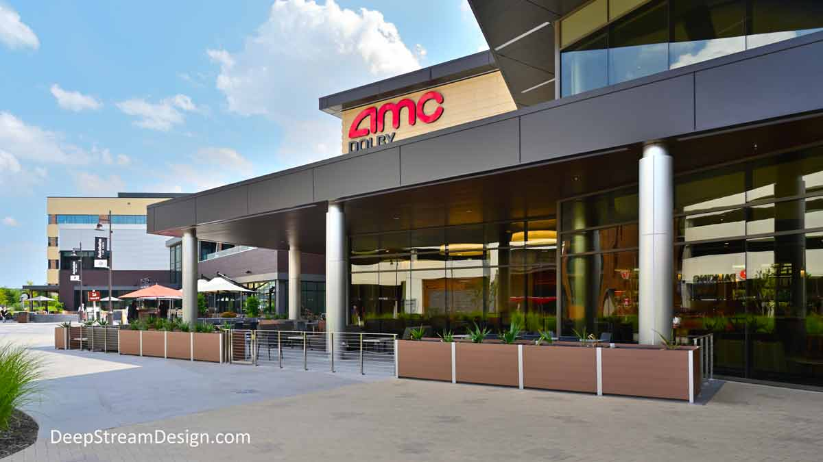 Large, commercial grade, rectangular Large Wood Garden Planters crafted with no-maintenance aged hardwood colored recycled plastic lumber, alternate with stainless steel cable railing to create an outdoor seating area in front of an AMC movie theater at a modern outdoor suburban mall.