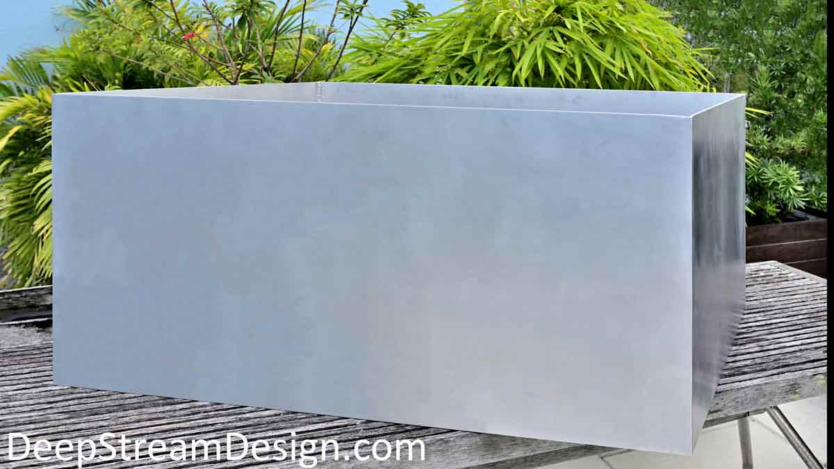 Large Planter for Trees constructed out of stiff 5086 marine alloy aluminum shown on a tropical roof terrace with green bamboo, palms, and podocarpus in the background.