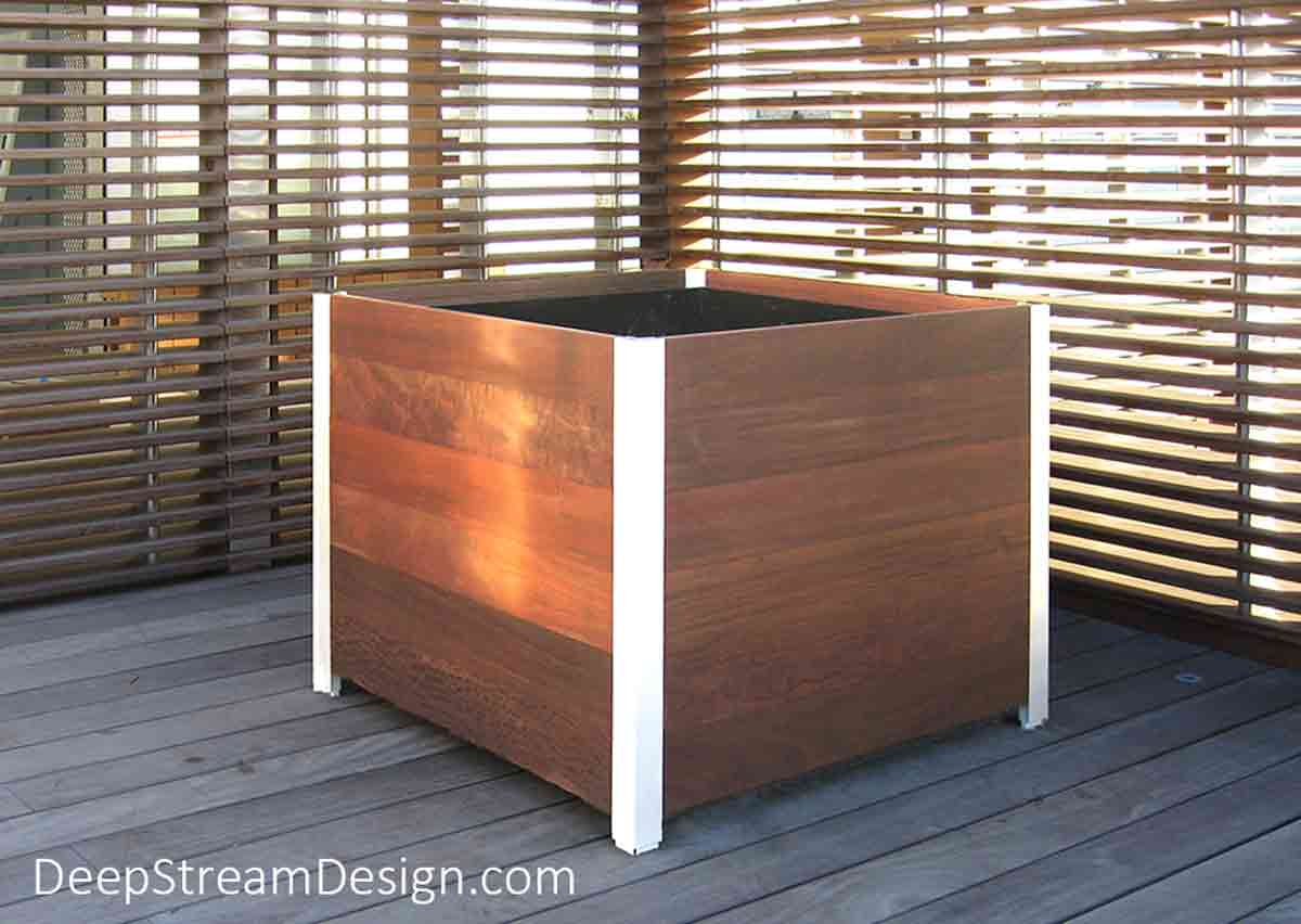"""An oblique profile view of an unplanted 36"""" cube shaped Large Wood Planter for Trees showing the ¾ inch thick planks held by anodized silver aluminum legs with a black plastic food safe inner planter liner just showing as the top of the liner is recessed about 1"""" below the edge of the top Ipe wood plank."""