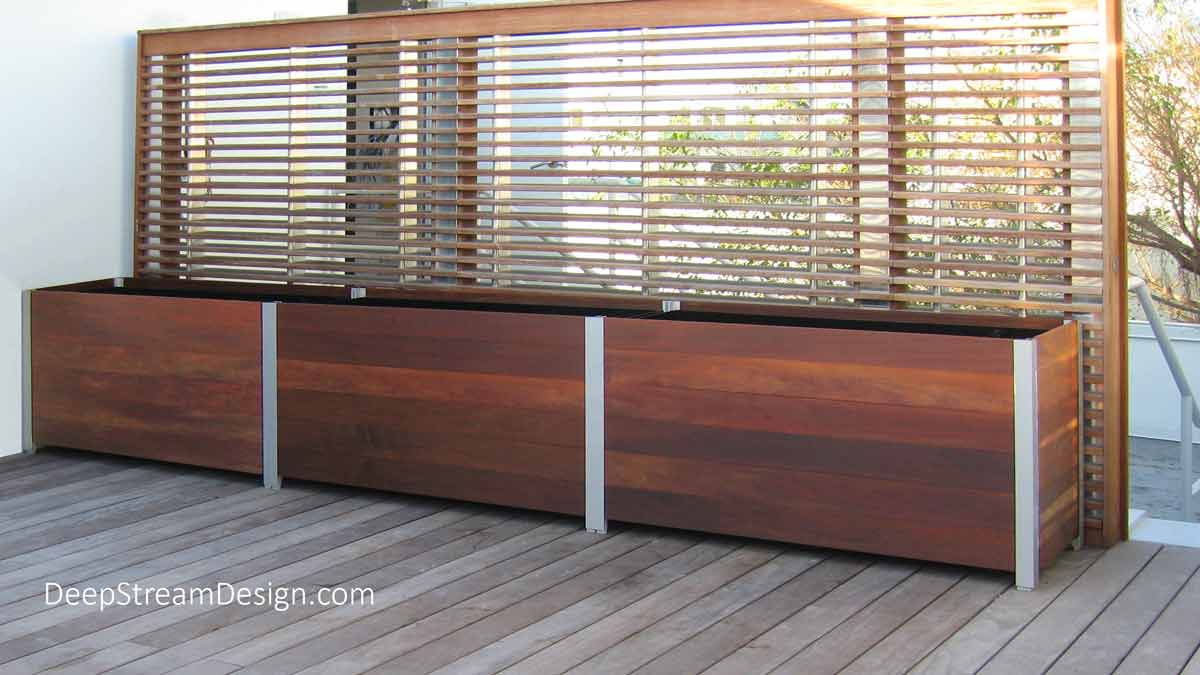 DeepStream's proprietary anodized aluminum legs and engineered frame system create modular Large Wood Planters for Trees in front of a wood screen wall atop a chic Miami boutique hotel.