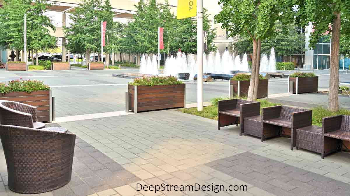 7 Large Wood Garden Planters landscape the perimeter of a fountain courtyard at the center of a large urban commercial development with tall trees lining the seating areas in front of shops and businesses.
