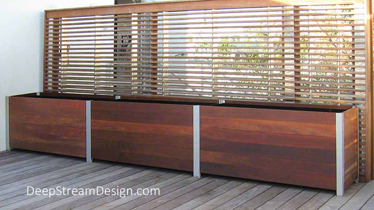Large Ipe Wood Garden Planters and planter liners in front of a wood screen wall on a hotel roof deck.