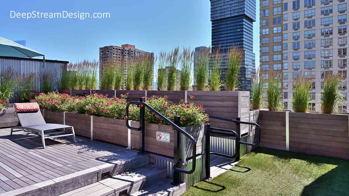 Large Wood Garden Planters filled with flowering plants and ornamental grasses used as parapet walls are a creative way to bring nature onto the urban terrace of a converted historic building surrounded by skyscrapers.