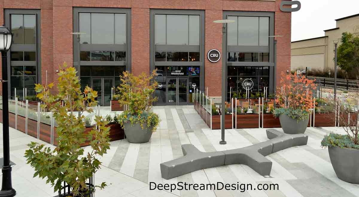 Large Wood Garden Planters with glass screen wall and planter liners, landscaped with bushes, creates an upscale outdoor urban restaurant on a plaza for a wine bar inside a modern brick building.