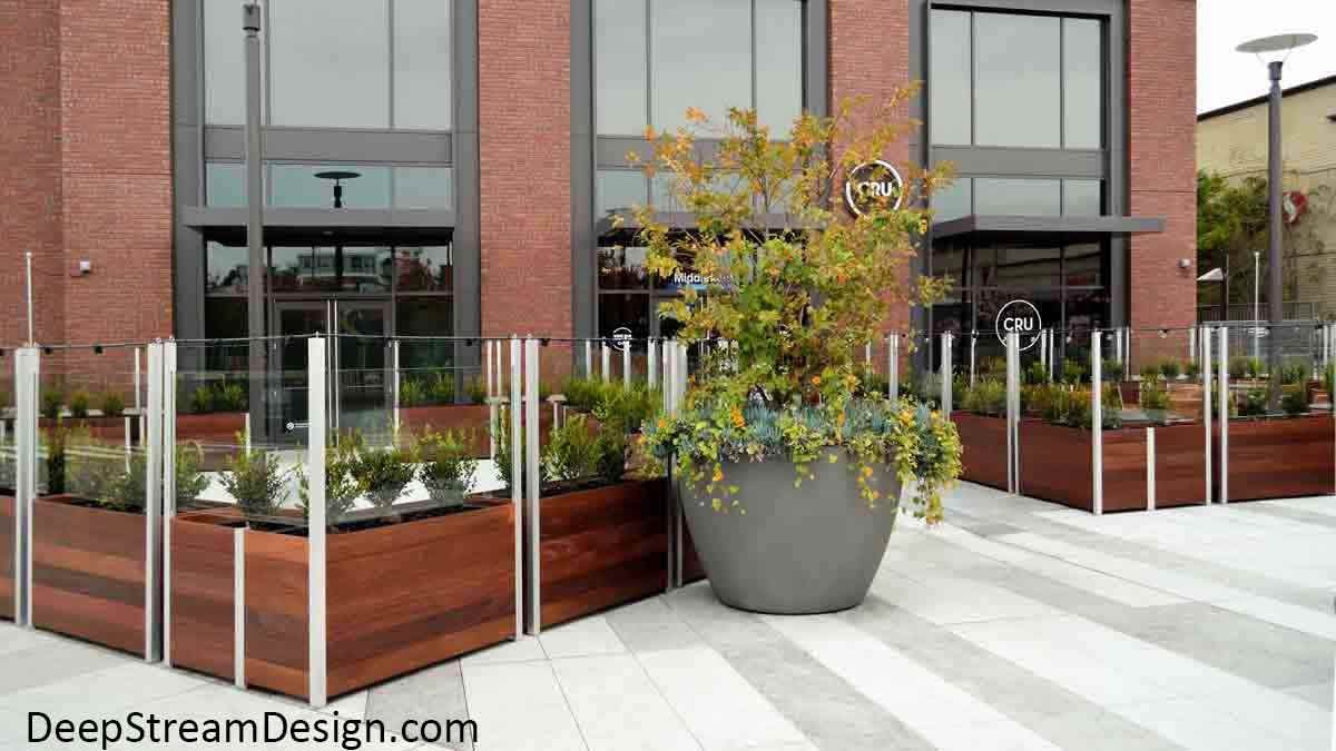 Large Wood Garden Planters with wheels and planter liners planted with bushes create a moveable modular glass screen wall for an upscale outdoor city restaurant on a city plaza.