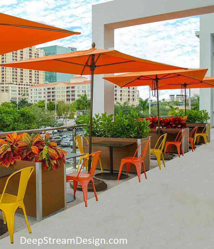Movable, maintenance free, redwood-colored recycled plastic lumber Large Wood Garden Planters on Wheels with planter liners separate tables under orange umbrellas along a restaurant outdoor balcony seating area.