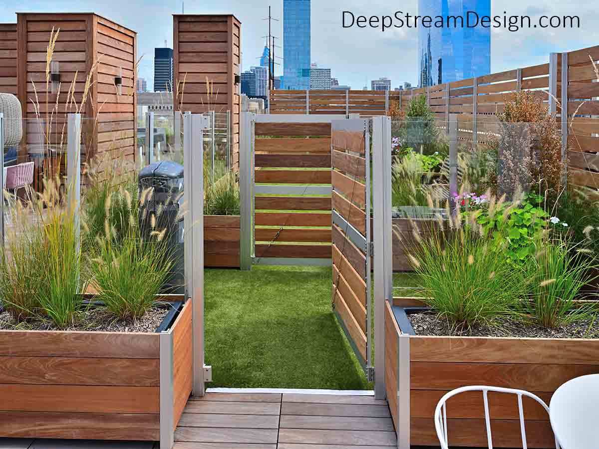 Large Wood Planters with gates anchor screen walls to create a roof top garden oasis of plants, flowers, and a regulation dog park with skyscraper views.