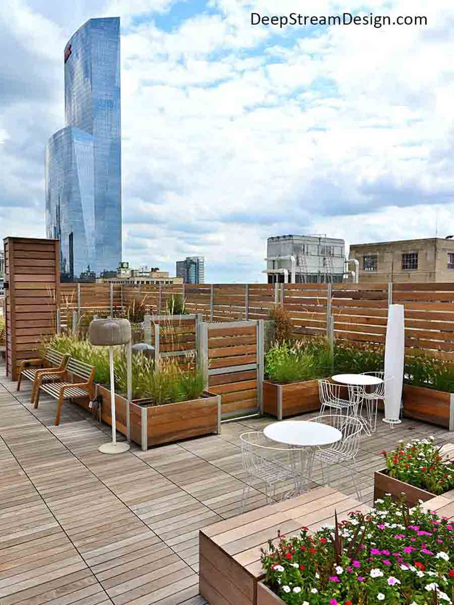 Large Wood Garden Planters anchor a glass and wood screen wall enclosure and parapet walls to create this apartment building's roof top garden BBQ seating area and dog park.