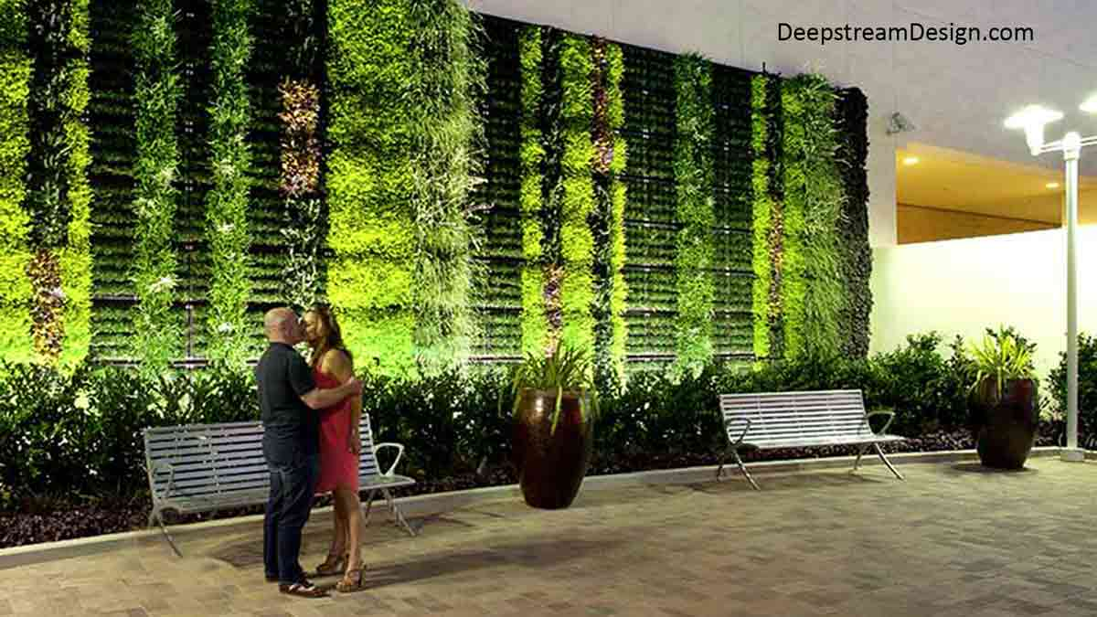 A standing couple kissing on a courtyard under the street lights with benches and a green wall mounted to the building behind them.