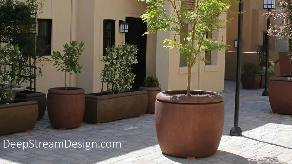 Extra-large, rounded rectangular, round and cube shaped earthen colored Metro Fiberglass Garden Planters landscaped with trees and flowering trellises fill a cobbled street courtyard.