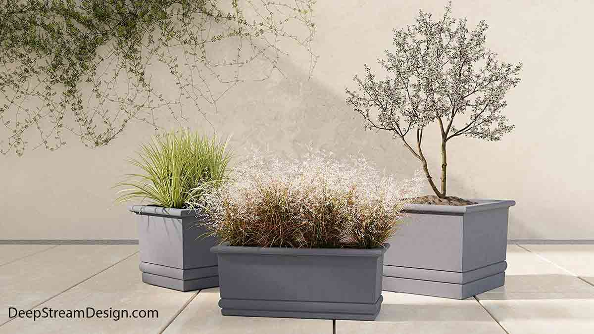 With a modern grey color, clean crisp molded top edge, and double reveal at the bottom of these large cube and rectangular high quality commercial concrete planters, the Florence Collection, available in 12 colors and 5 textures, represents modern restrained Italian design. These extra large rectangular and cube concrete garden planters, landscaped with trees, bushes and ornamental grass add an Asian aesthetic to this elevated marble outdoor terrace.