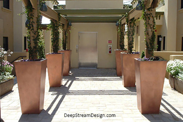 Six tall copper-colored tapered Modern Planters flank the entrance walkway under a pergola to an elevator, making for a dramatic entrance.