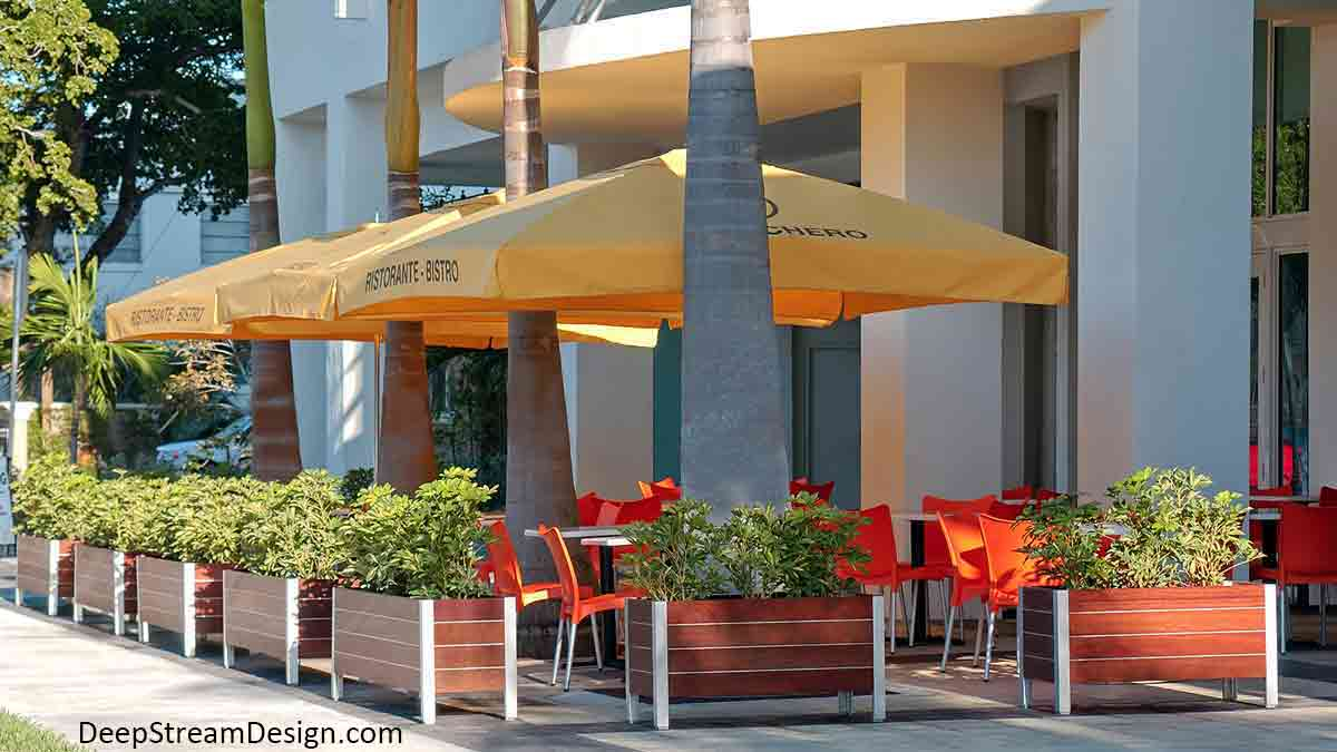 A series of Modern Planters create a modern tropical Miami sidewalk cafe with bright orange chairs under palm trees and bright yellow bistro umbrellas.