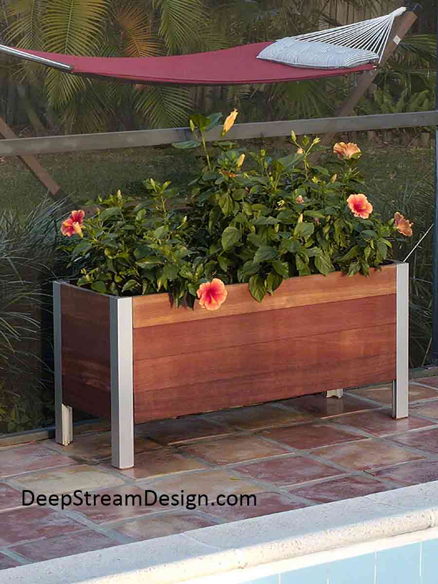 A Modern Planter handcrafted of Cumaru wood in a residential setting between a cool blue tropical pool and a hammock hanging in a lush green shaded garden under palm trees.