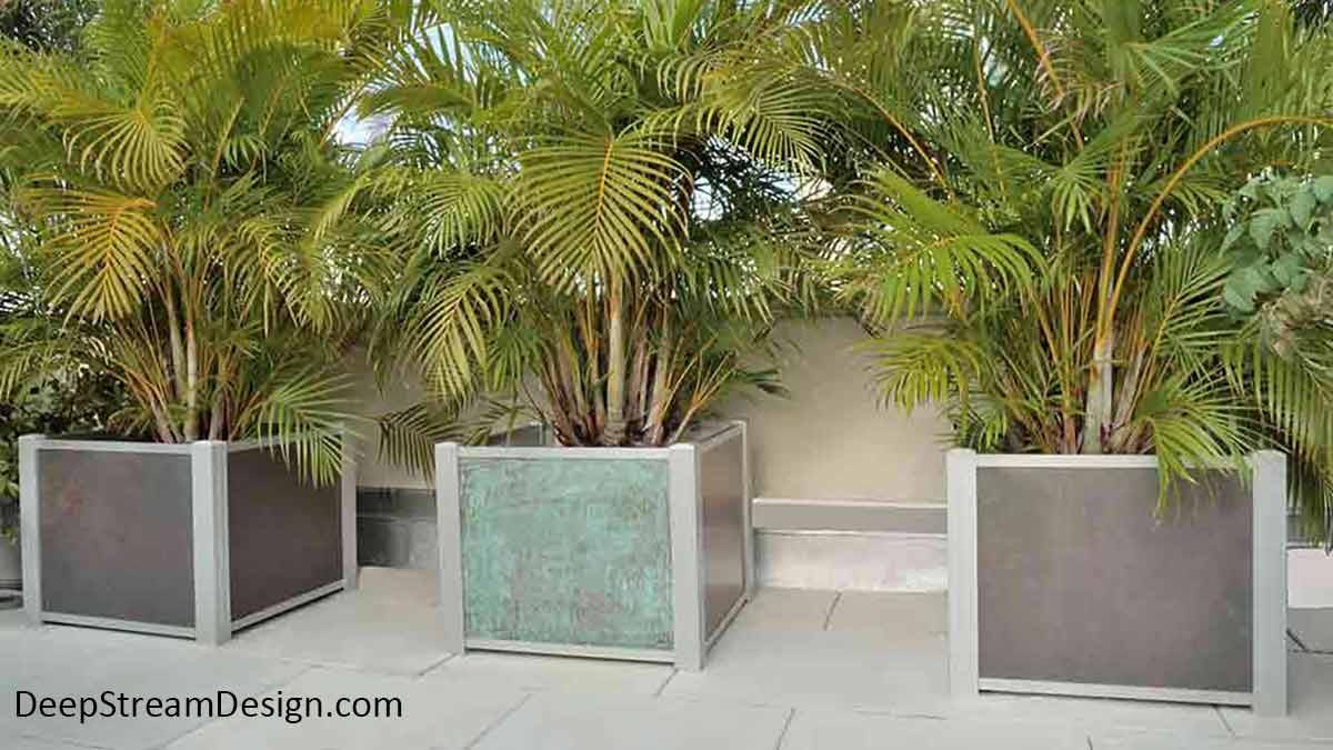 Three Modern Planters landscaped with feathery palms inside planter liners. Two modern planters crafted with dark natural slate flank a modern planter with copper panels on a the tropical roof deck of a Miami penthouse. DeepStream's Audubon anodized aluminum extrusions hold panels of any material, thick or thin.